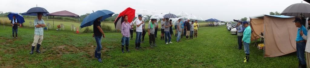 小雨の中の開会式、選手は傘をさして参加、説明に聞き入る。